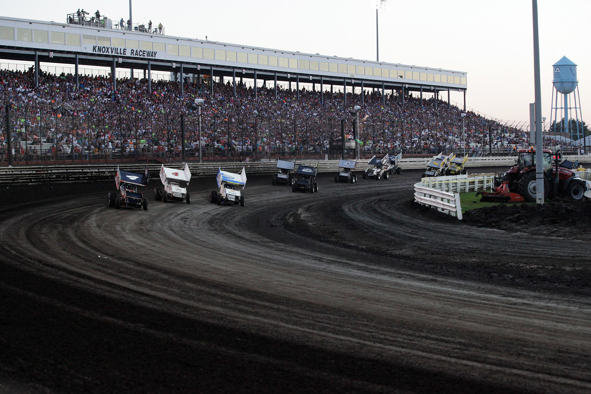 Left to right, No. 4 Jon Agan, No. 4S Danny Smith and 23C Tyler Courtney go 3 wide into turn 1 in the E Main on the final night of The Knoxville Nationals. ( Jeffrey Turford / TDP )