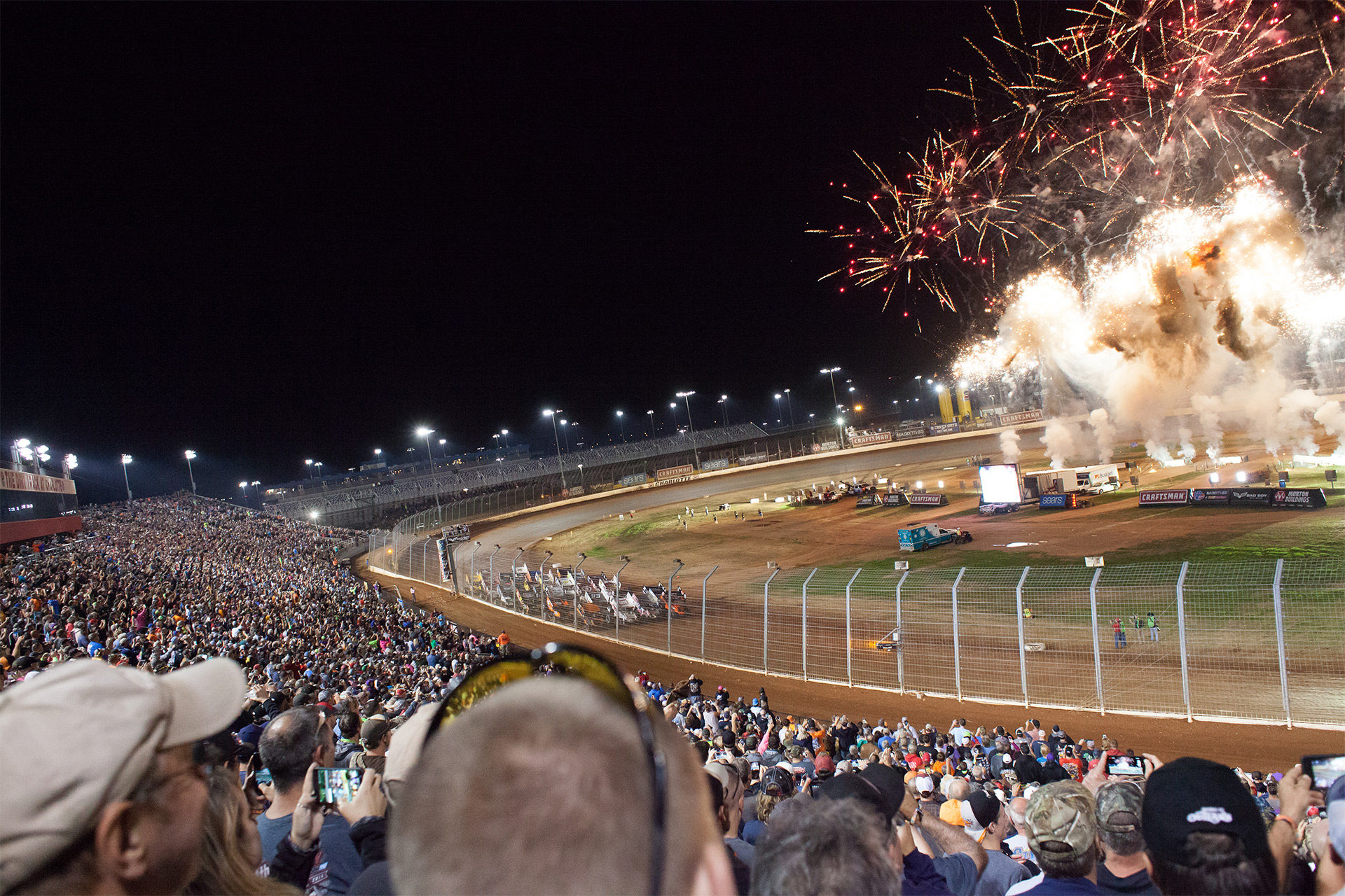 Fireworks light-up the 19 car field, in anticipation for the green, during the Feature race Saturday night, Day 2 of The Bad Boy Off Road World of Outlaws World Finals at The Dirt Track at Charlotte, in North Carolina 2016. ( Jeffrey Turford / TDP )