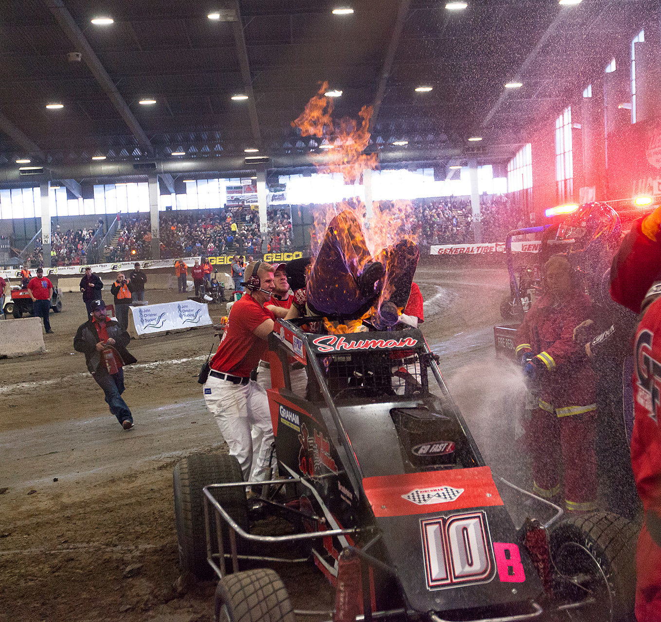 Saturday January 14, TULSA, Oklahoma - With Rick Shuman set ablaze, courageous Lucas Oil track staff rip him from the car, saving the driver from serious injury ( Jeffrey Turford / TDP )